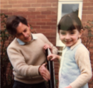 Liz as a child helping her dad in the garden